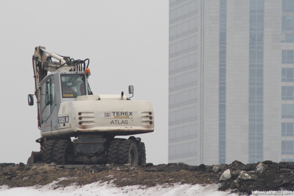 Digging machine operating on the mine waste dump against the background of the Altus building